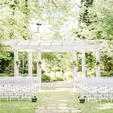 Outdoor white pergola with seating set for wedding amidst trees