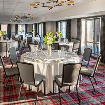 Round tables set for event in room with scarlet and gray plaid carpeting