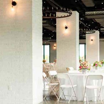 Round tables set for wedding amidst lighted pillars